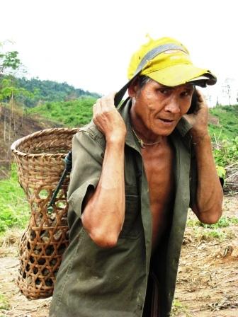 Alter Mann schleppt die schweren Steine den Hügel hinauf