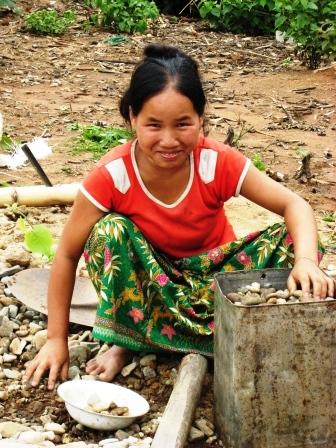 Frau füllt Behälter mit Steinen für den Bau des Wassertanks
