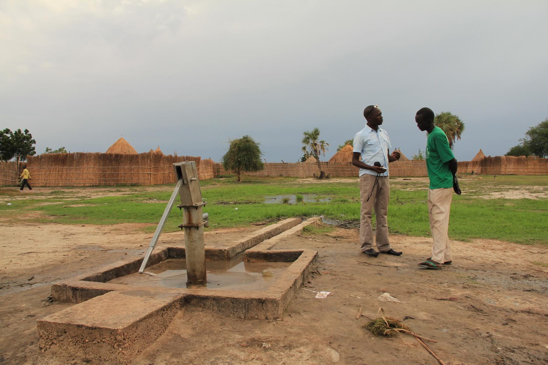 David Mitu, SSRC WatSan coordinator assess a water site