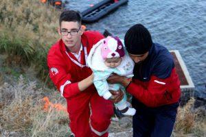 Ein Rescuer, der Kind und Vater vom Boot an Land hilft.
